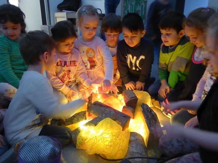 Kinder sitzen am Lagerfeuer